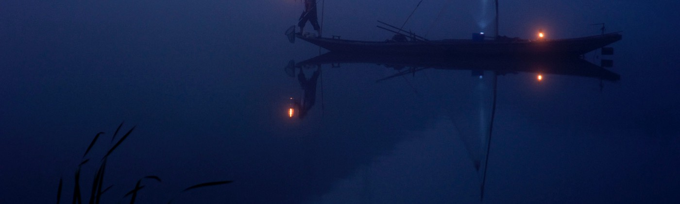 A boat in darkness, illuminated by lanterns