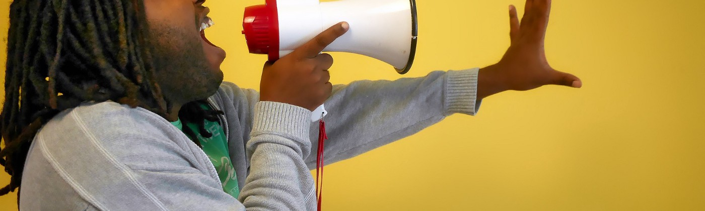 a dark brown skinned person with shoulder length dreadlocks shouting into a megaphone with their hand outstretched in front