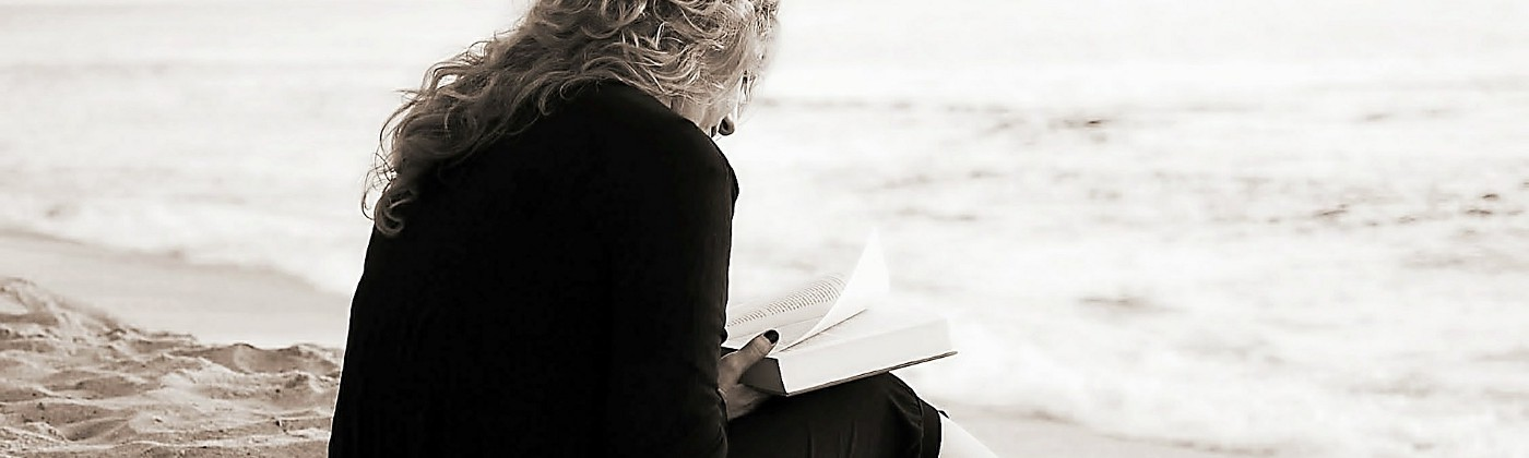 woman with bare feet sitting and reading on the beach