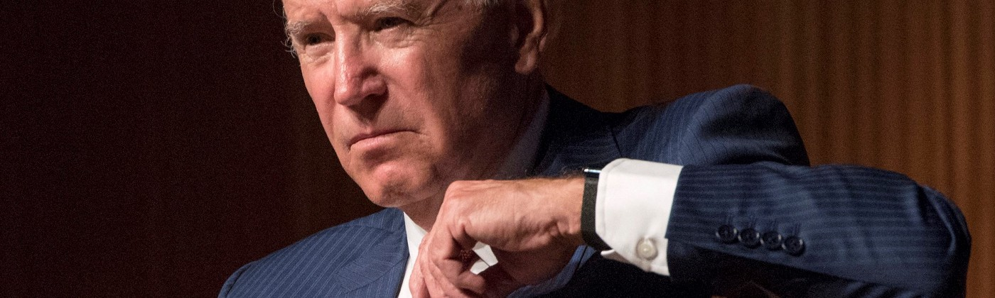 Joe Biden—old white man with white hair—wears a suit and looks off to the side with a serious look on his face