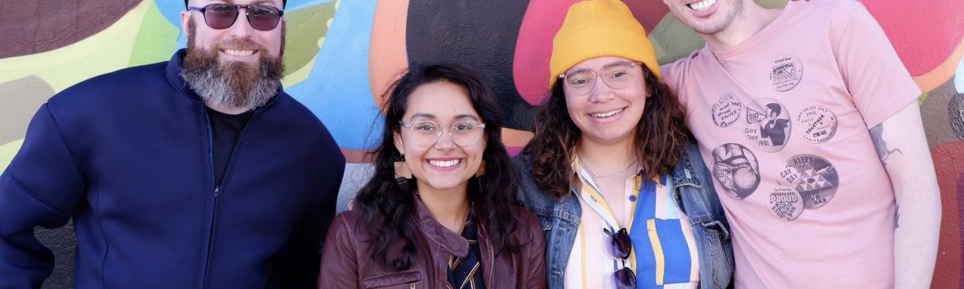 A smiling group of four queer design club members in front of a colorful mural in the Mission.