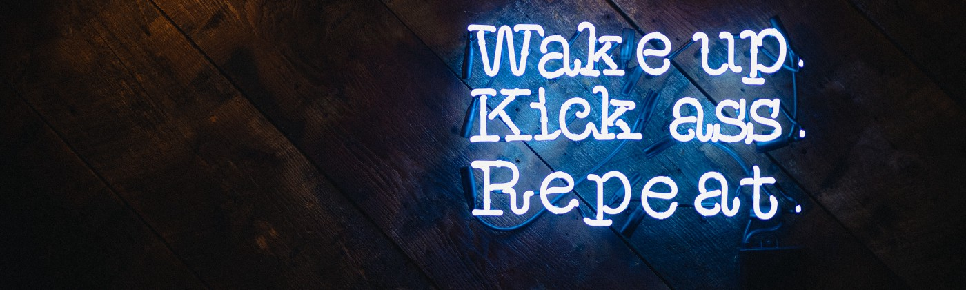 Right centered neon lit sign that reads: Wake up. Kick ass. Repeat.