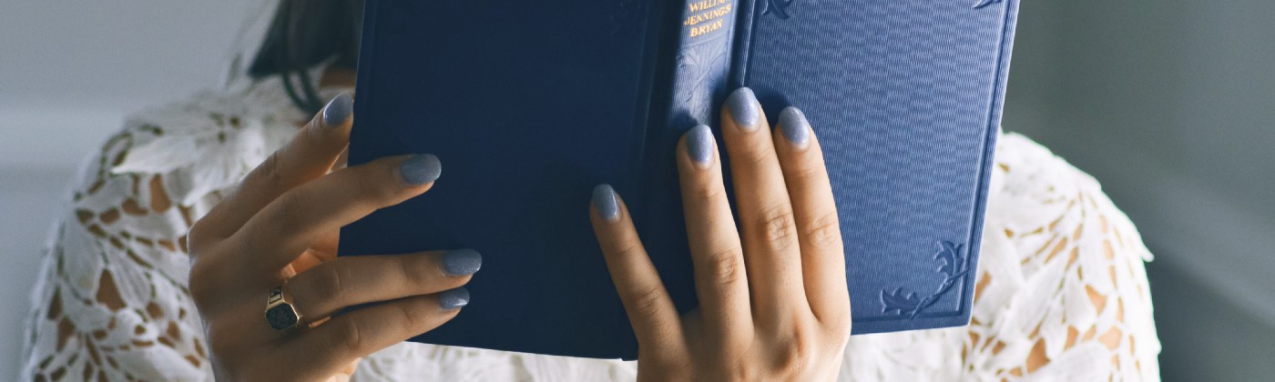 Woman reads book with blue cover
