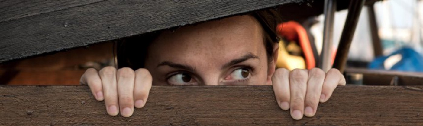 A woman hiding and peeking out of the structure she is in.