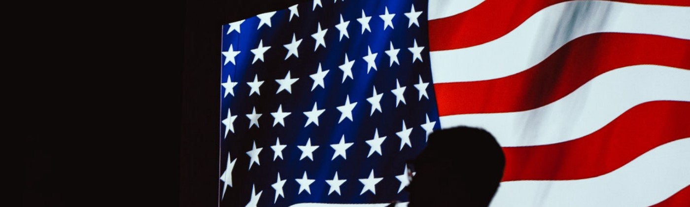 United states flag with shadow of people standing in front of it.
