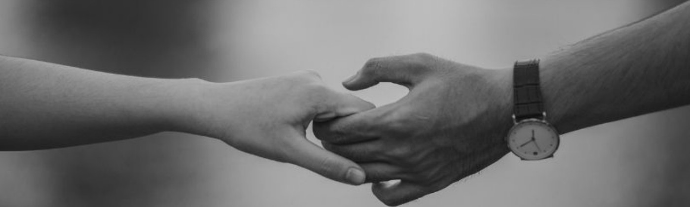A black and white photo of a woman and a man holding hands showing just the hands and wrists