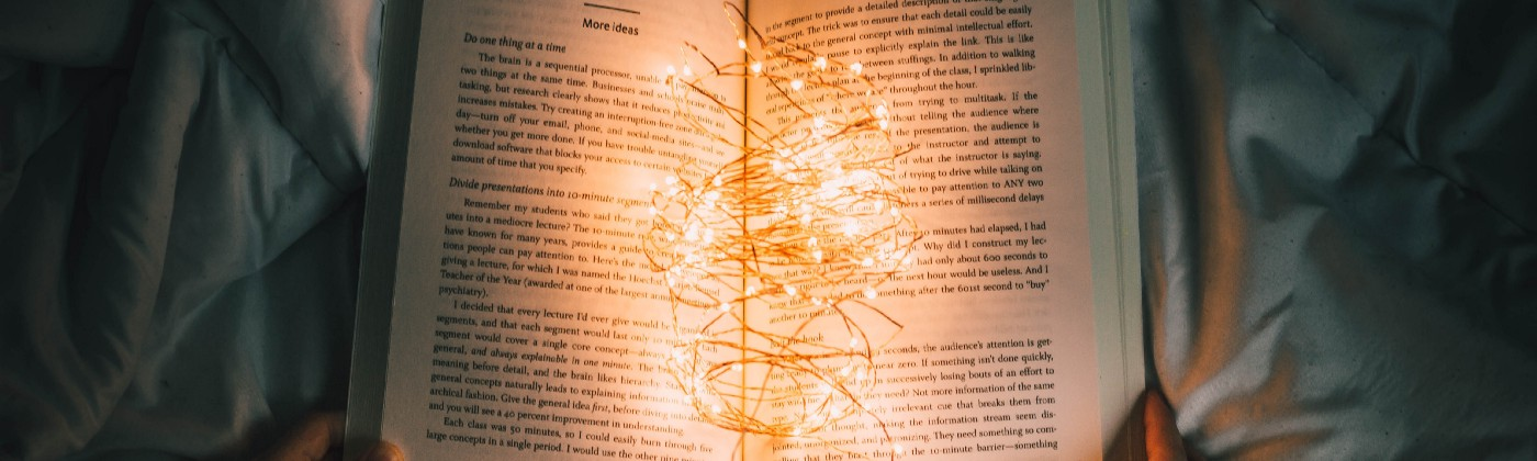 An open book illuminated by a string of lights