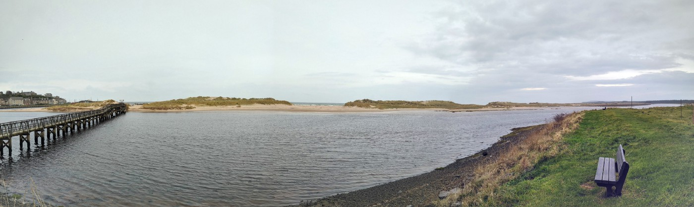A panoramic scene of Lossiemouth bridge and beach with sand dunes beyond the water