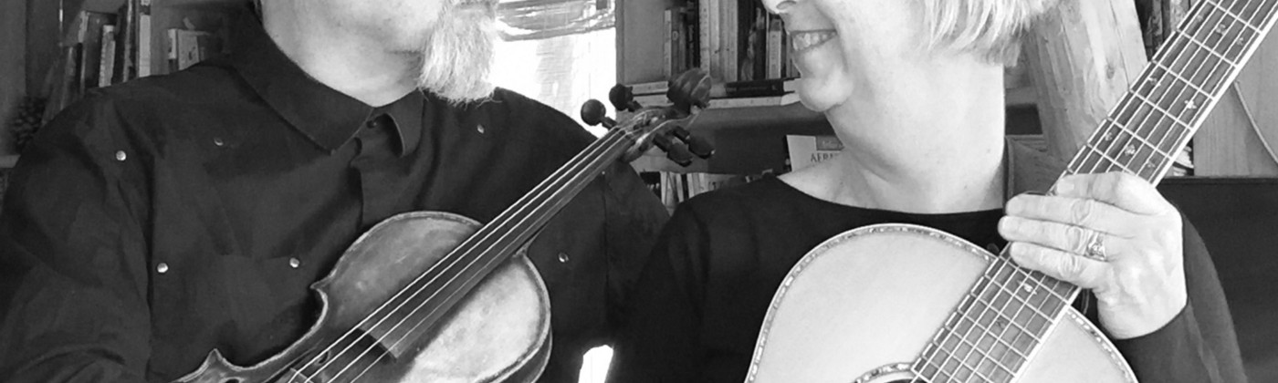 Two sixty-something musicians look at each other while holding a guitar and fiddle.