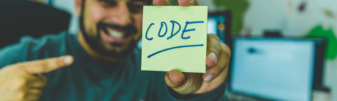 Smiling man showing sticky note with code illustration.
