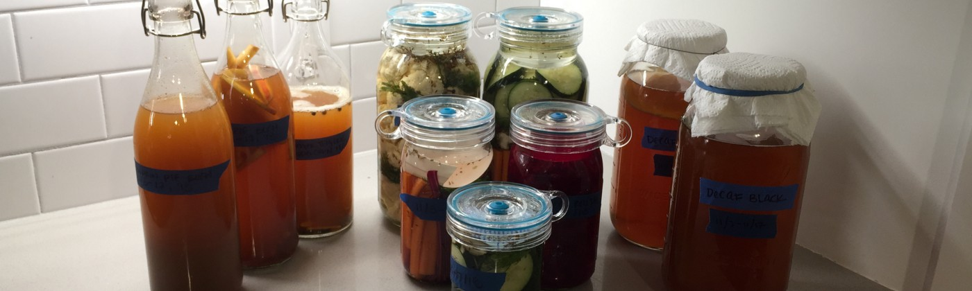 The pickle fleet in full force. Kombucha and pickled vegetables fermenting in jars.