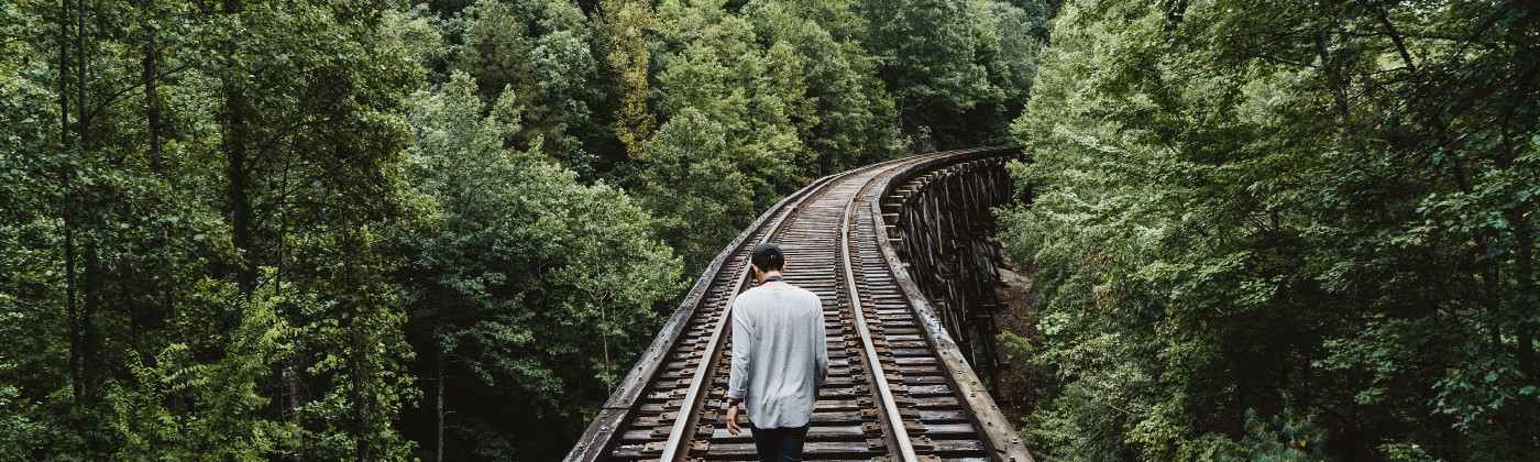 Solitude: Man alone by choice, walking on railroad tracks
