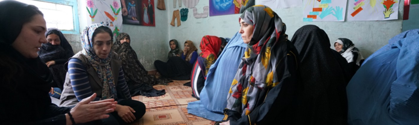 A group of women wearing colourful head scarves sit on the floor in conversation.