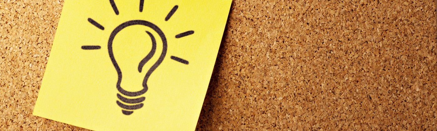 A yellow Post-it Note with a drawing of a lightbulb tacked onto a cork board.