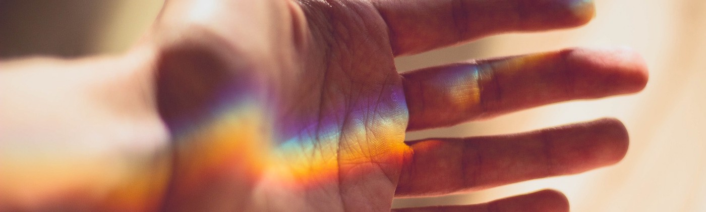 hand bathed in the rainbow light from a prism