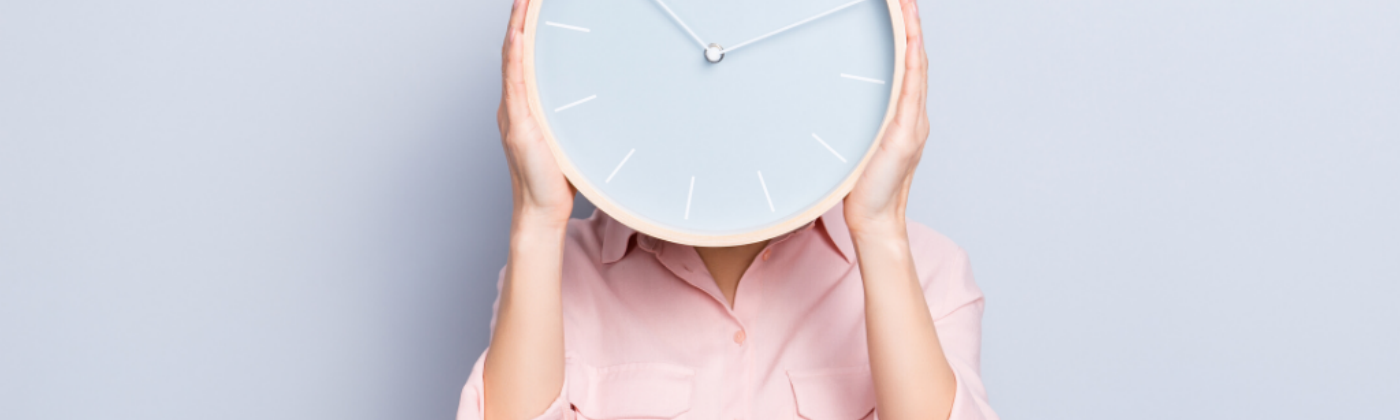 Time Management: A women holding a clock in front of her face