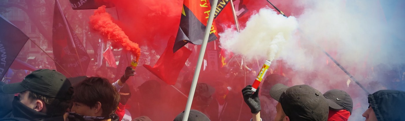 Communists and anarchists protesting in a cloud of red smoke in Switzerland