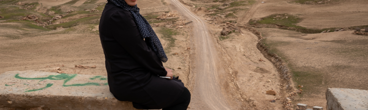 A woman dressed in black sits on a low wall opening to a dirt road into the desert. She is facing the camera and smiling.