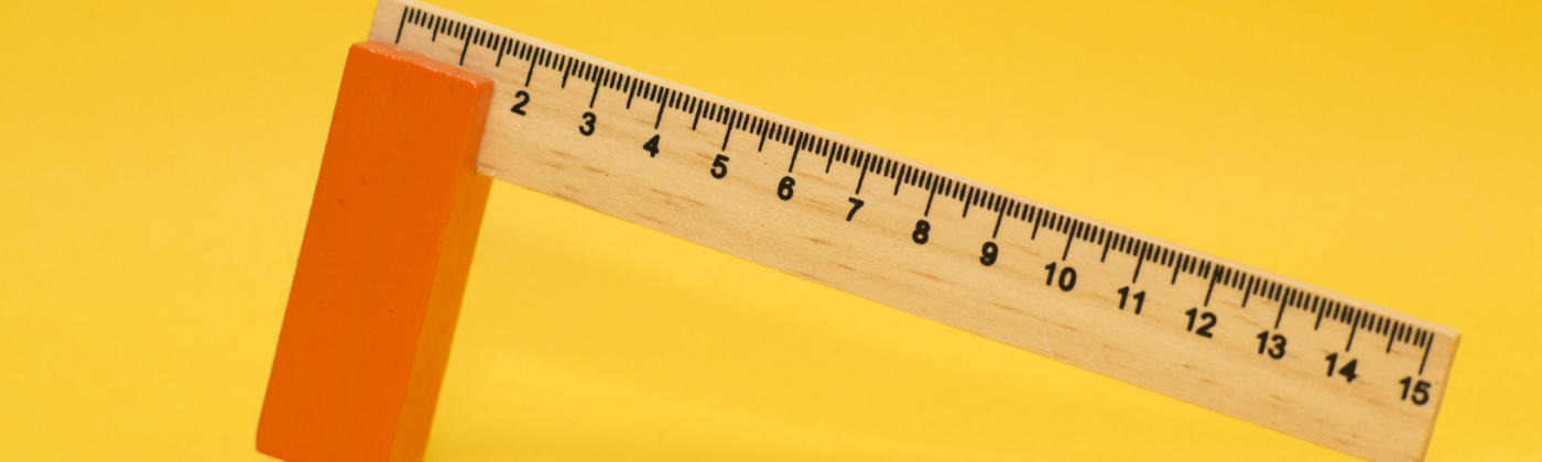 Wooden ruler with holder on a bright yellow background.