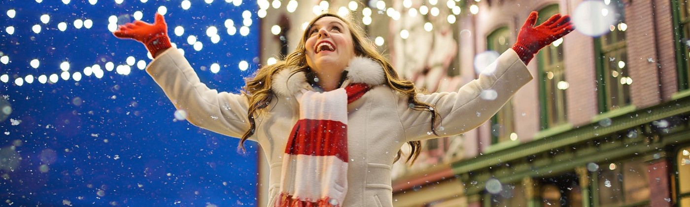 Women wearing a white coat, red gloves, and red and white striped scarf in the midst of a city street decorated for Christmas