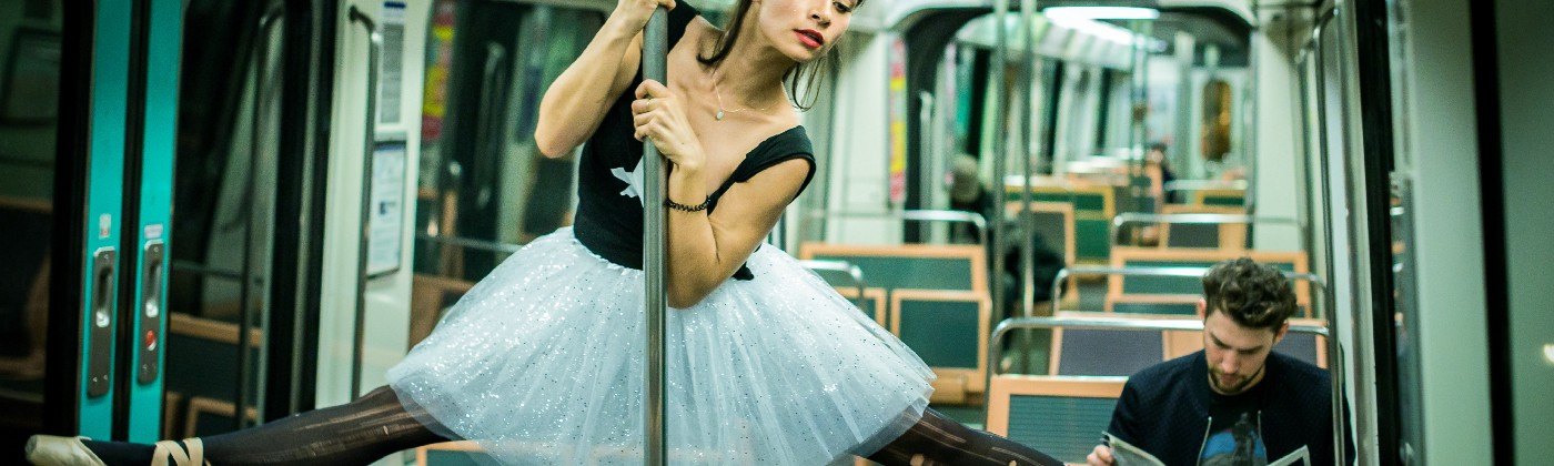 Ballet dancer in tutu performing in an underground train. Guy sits on seat, reading, completely uninterested in her