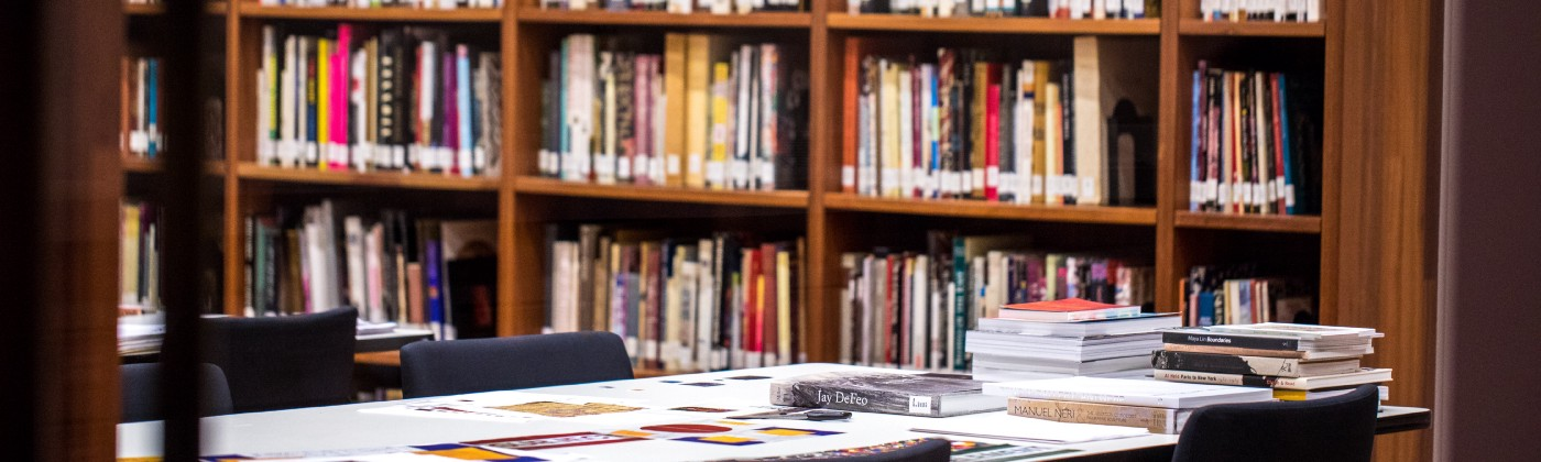 Stacks of full shelves in a library, table full of study materials