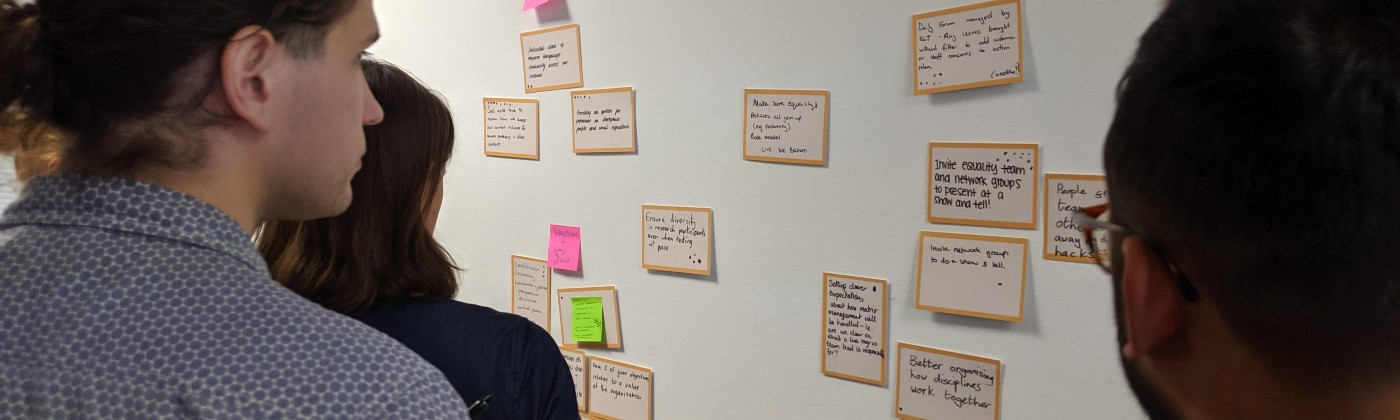 People gathered around a wall full of Post-its, each containing short statements describing an idea
