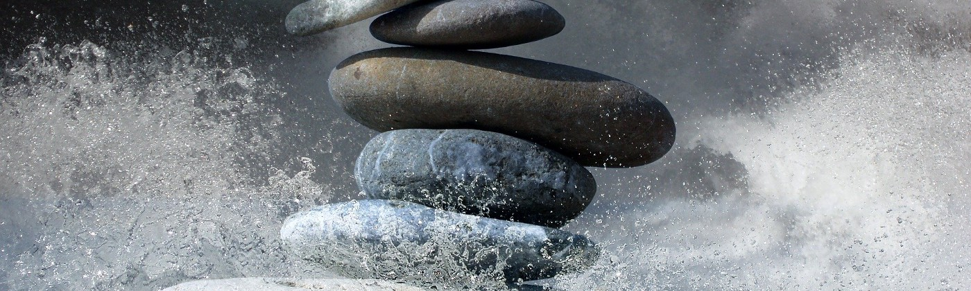 A stack of stones balanced atop each other in ocean spray.