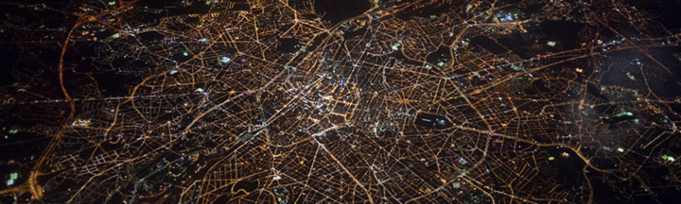 An aerial view of a city, the streets illuminated by lights.