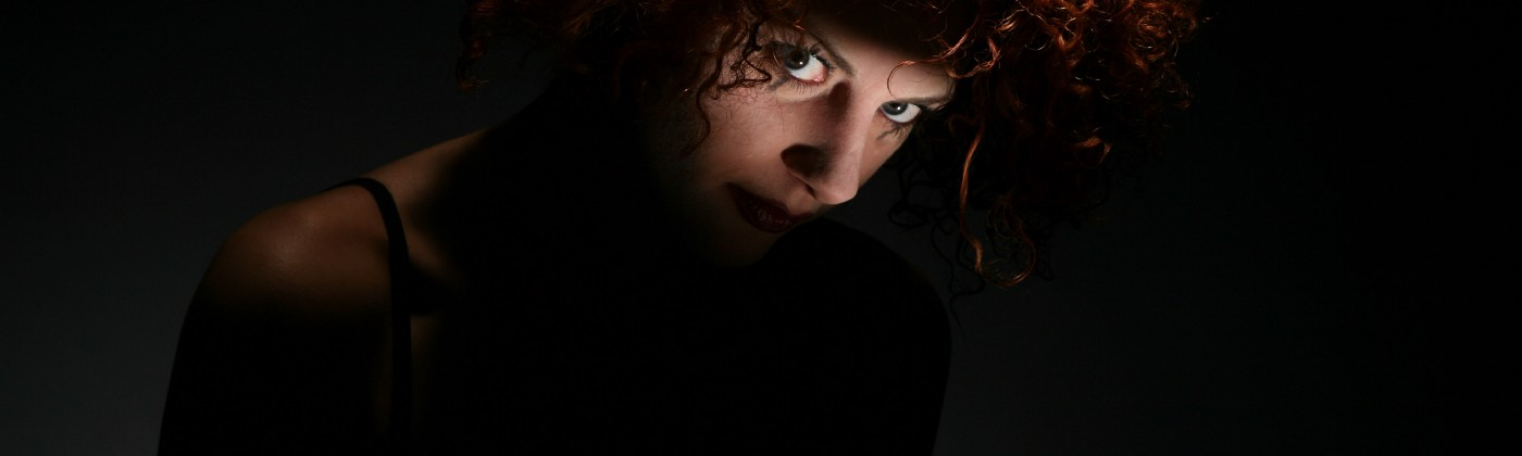 Woman in the dark with light shining on her eyes as she stares at the camera intensely
