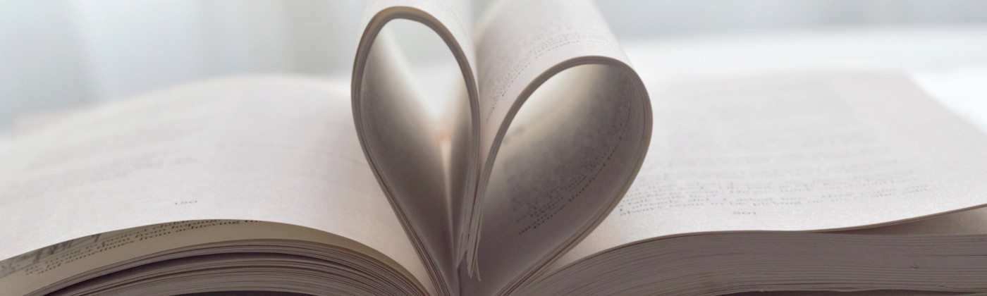 a book sits open and in profile; the middle pages are folded inwards to create a heart-shape