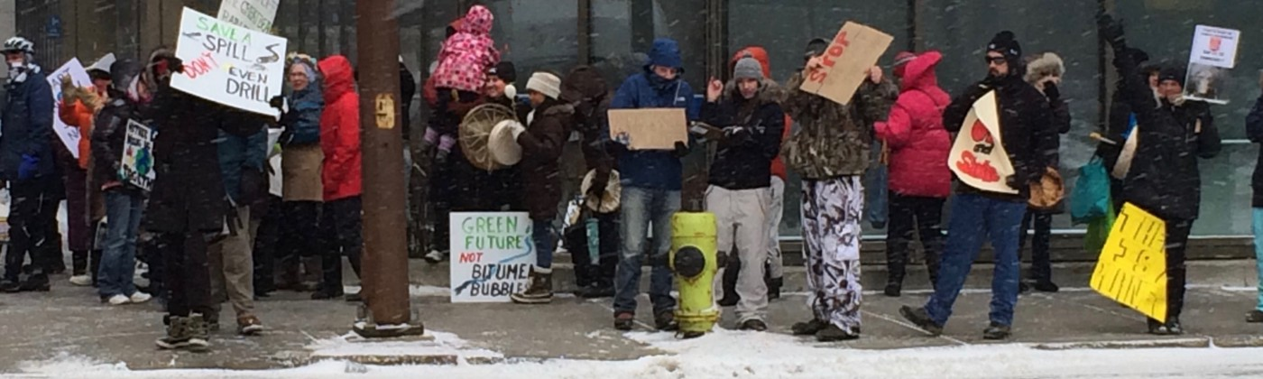 Protestors along a sidewalk, mostly dressed in winter garb, with placard signs and drums, while snow is falling.