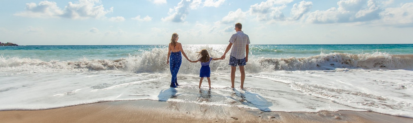 Beach with a wave, blue skies, couple with child facing the sun and waves