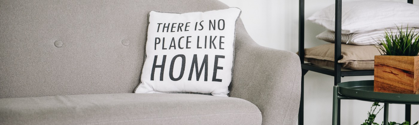 """An quiet room with a grey couch, on which there is a pillow that reads """"There is no place like home"""""""