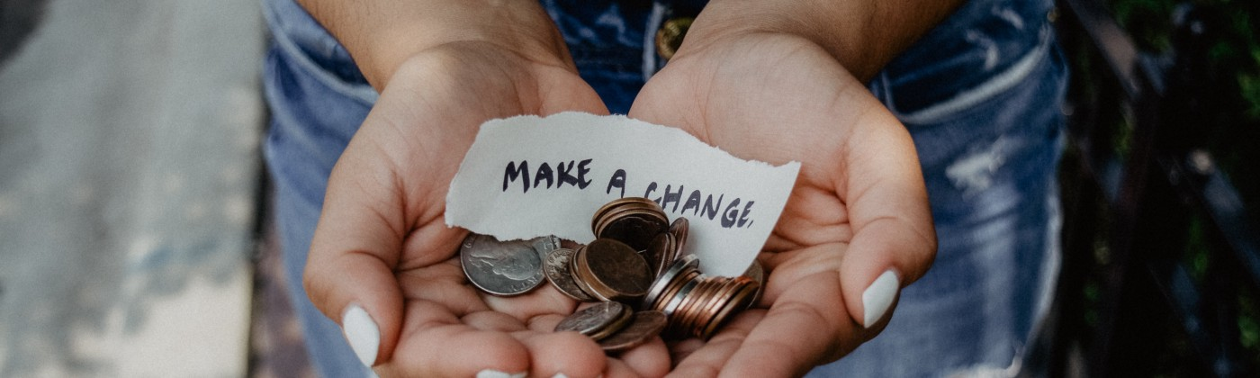 Woman holding coins in her hand with a piece of paper stating make a change