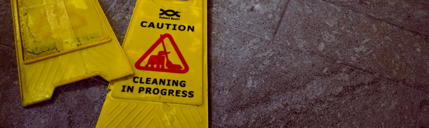 Yellow Caution—Cleaning in progress signs on tiled floor.