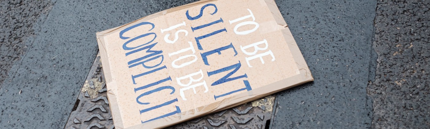 "Image of a protest sign on the ground saying ""to be silent is to be complicit"""