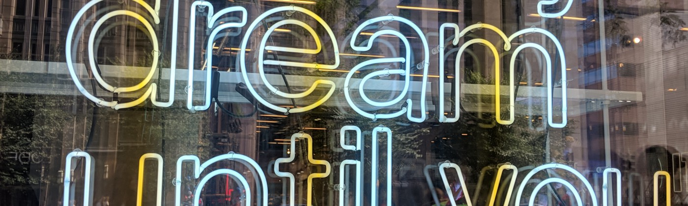 """Neon display in a store window that reads """"It's only a crazy dream until you do it."""" Nike—downtown Chicago—fall 2018."""