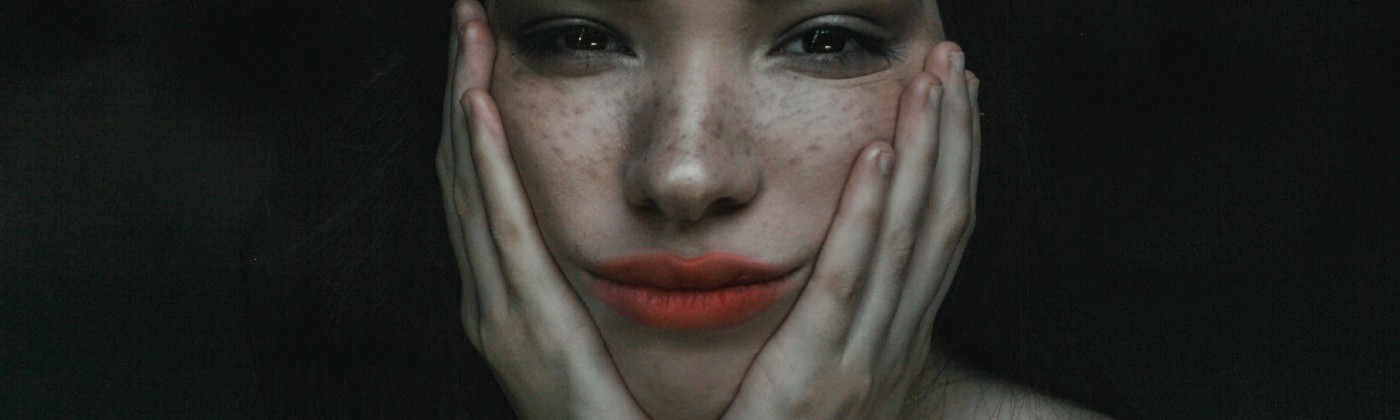 Freckled woman with dark hair and red lipstick puts hands to face in frustration
