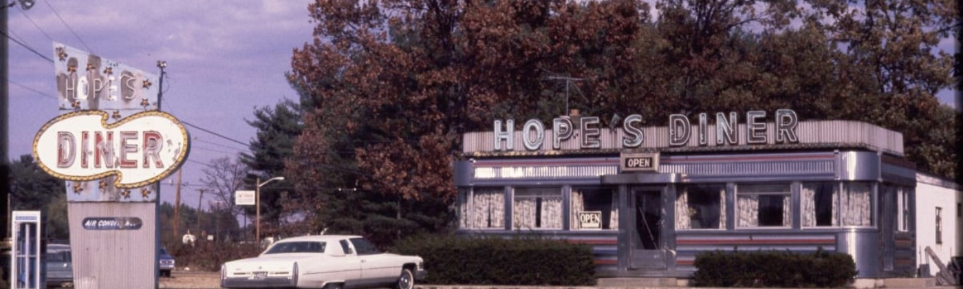 """Small building at right with silver letters spelling """"Hope's Diner""""; sign with same words to left. White car parked in front."""