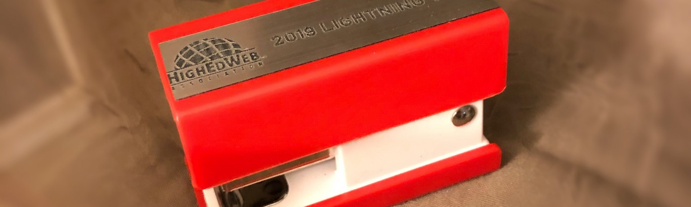 """Miniature red stapler with """"2019 Lightning Talk"""" and High Ed Web Association logo on top."""