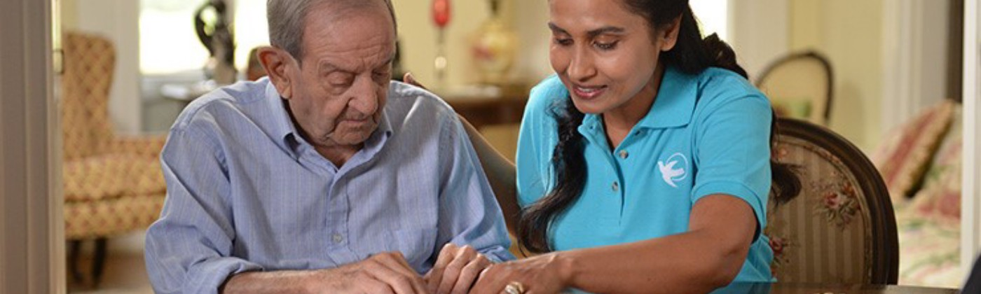 home care aide plays jigsaw puzzle with elderly man