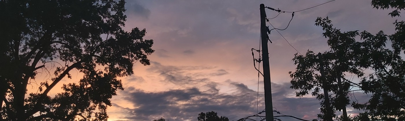 A picture of a blue, grey and amber sunset over the top of building