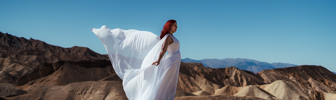 A woman dressed in a white flowing dress, which is blowing in the wind. She is standing on a rocky hill in desert terrain.