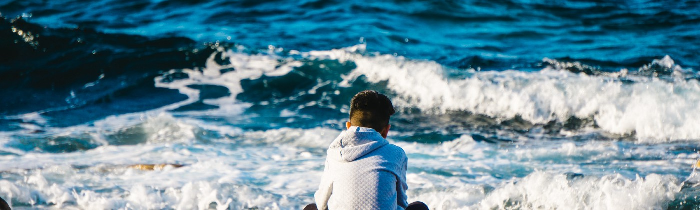 Boy sitting alone on a beach. He's facing away, to the crashing waves.