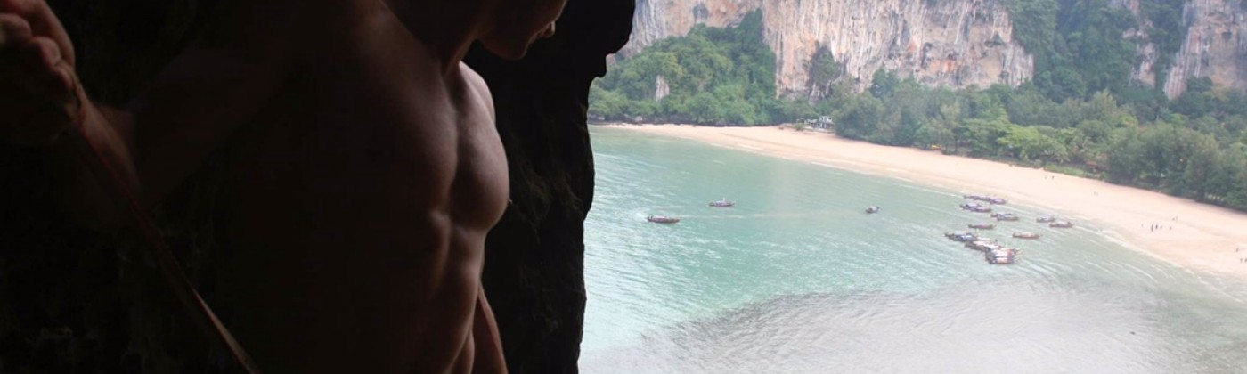 A man in a climbing harness looks down on a Thai bay