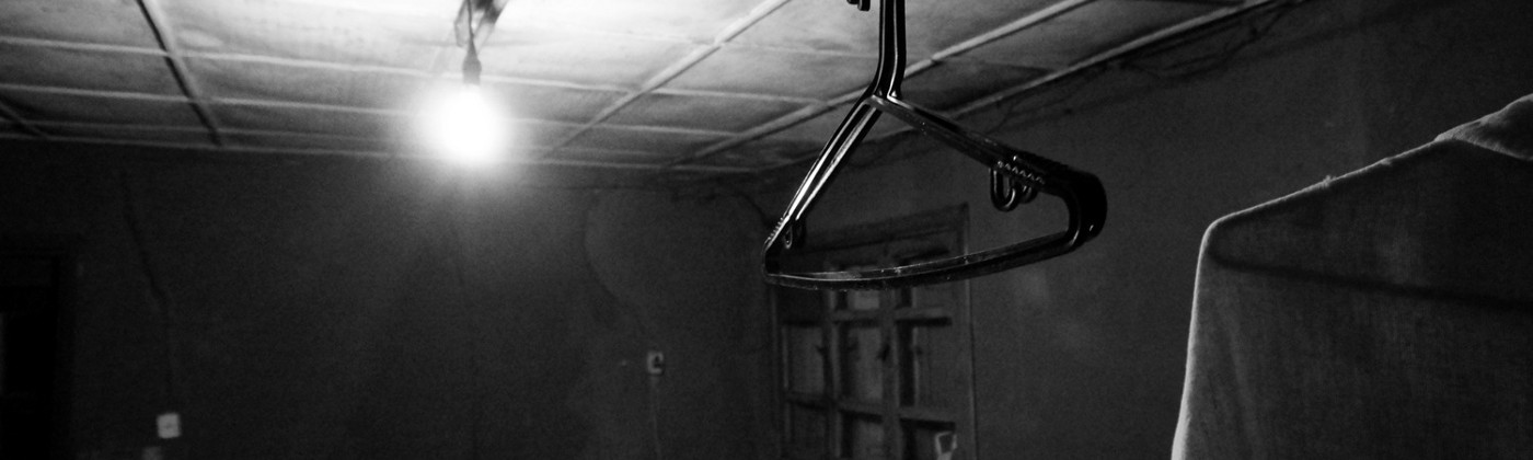 A B&W picture of a clothesline in an old kitchen. The kitchen was the place where families congregated their live on.