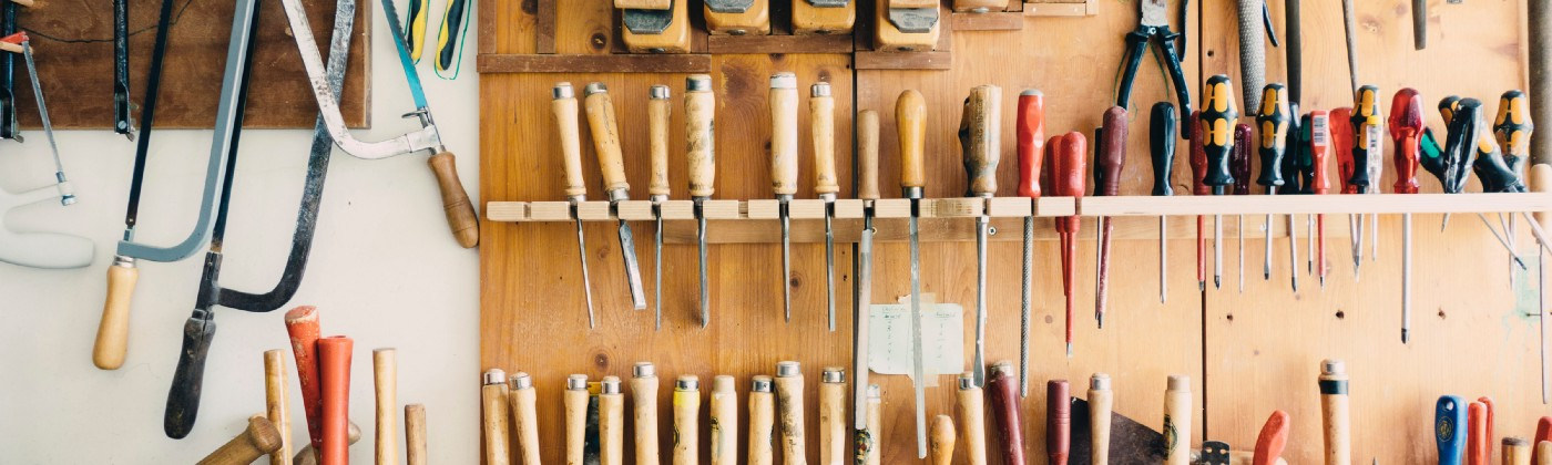 Carpenters workshop with tools on rack.