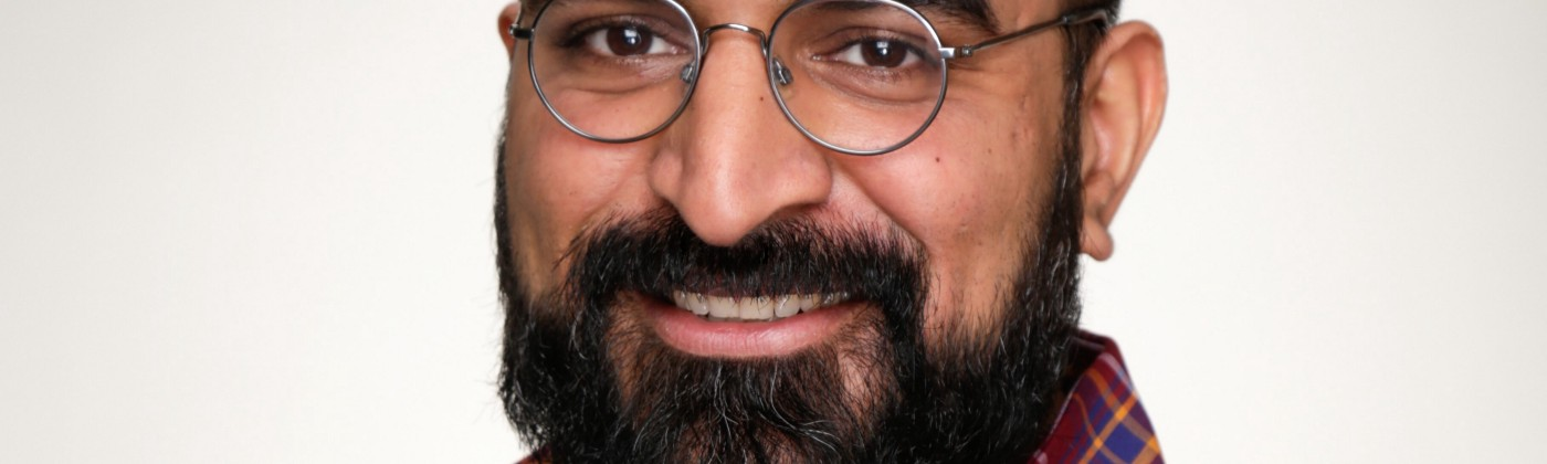 Headshot of a smiling man with black hair and a beard, and round glasses.