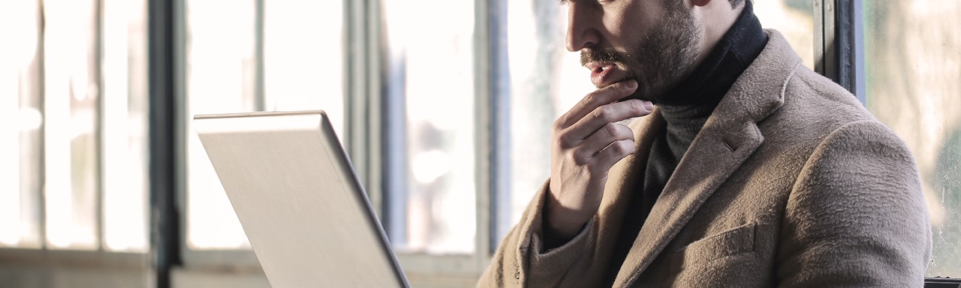 Man holding chin looking perplexed at laptop screen.